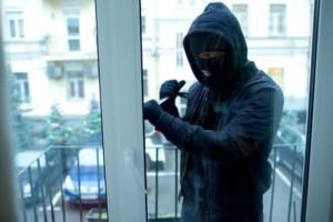 窓のカギをこじ開けようとする窃盗犯のイメージ